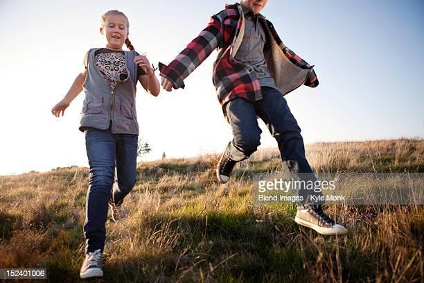 Caucasian children running in field