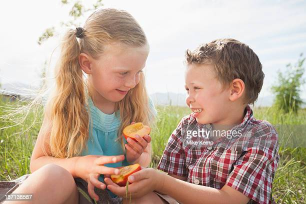 Caucasian children sharing fruit outdoors