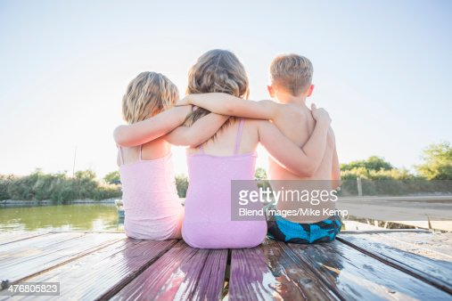 Caucasian children sitting on dock
