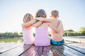 Caucasian children sitting on dock