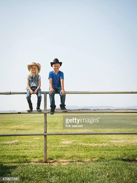 Caucasian children sitting on fence on farm