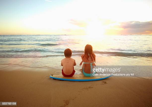 Caucasian children sitting on surfboard on tropical beach