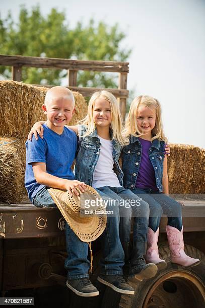 Caucasian children sitting on truck on farm