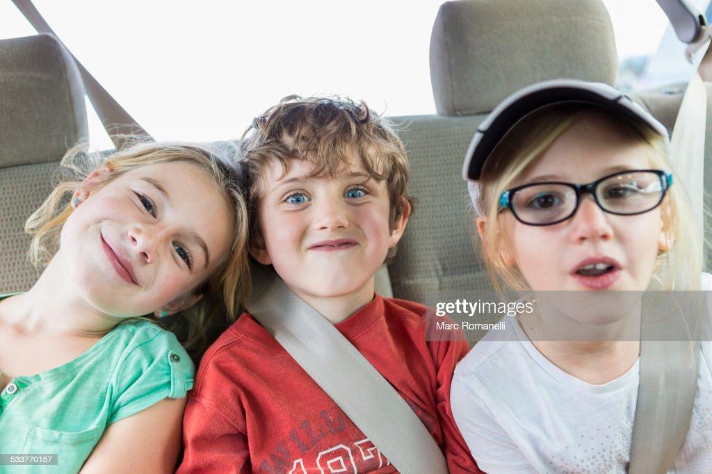 Caucasian children smiling in back seat of car
