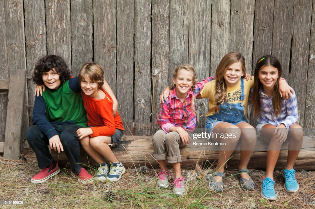 Caucasian children smiling together on wooden log