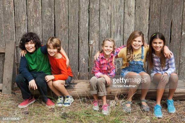 Caucasian children smiling together on wooden log