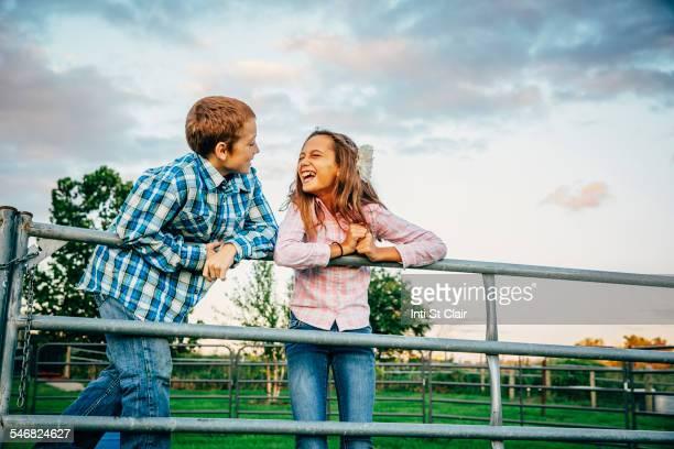Caucasian children standing on fence on farm
