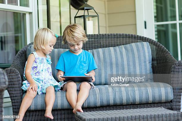 Caucasian children using digital tablet on sofa