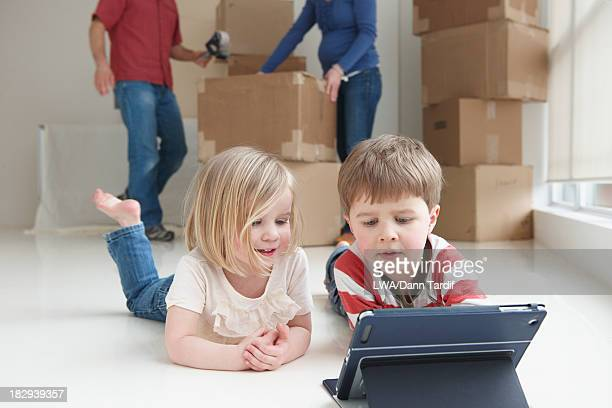 Caucasian children using tablet computer in new home