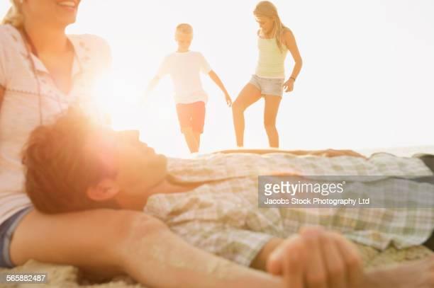 Caucasian children walking near relaxing parents outdoors