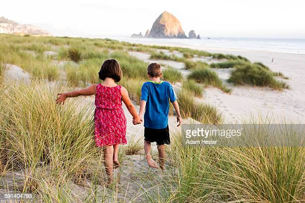 Caucasian children walking on beach