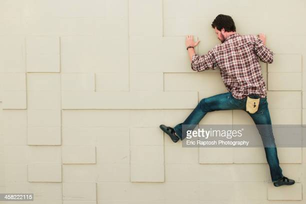 Caucasian climber scaling geometric wall