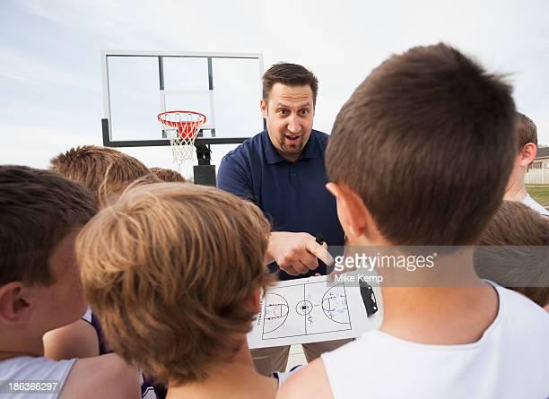 Caucasian coach talking to basketball team