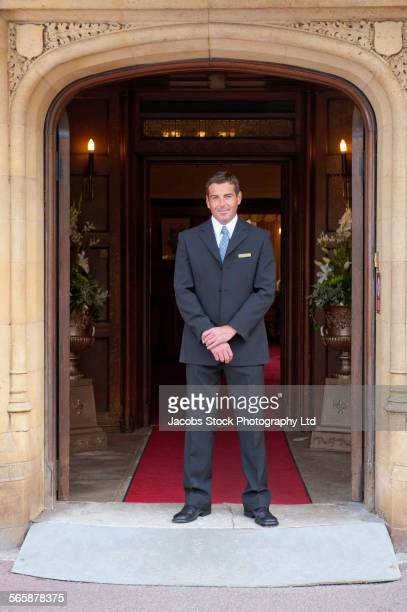 Caucasian concierge smiling at hotel entrance