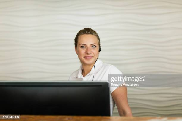 Caucasian concierge smiling behind hotel front desk