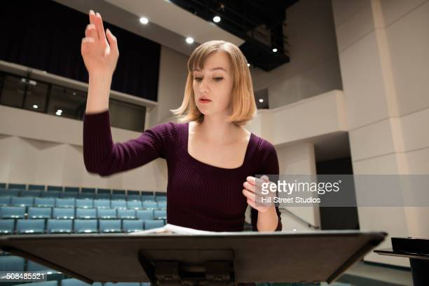 Caucasian conductor gesturing at podium