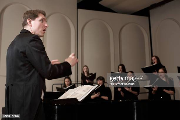 Caucasian conductor leading choir on stage