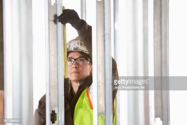 Caucasian construction worker measuring steel
