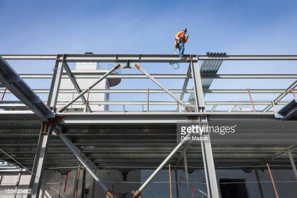 Caucasian construction worker standing on girder