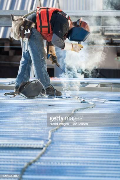 Caucasian construction worker welding floor