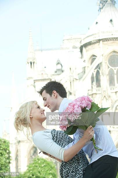 Caucasian couple about to kiss near historical landmark near Notre Dame