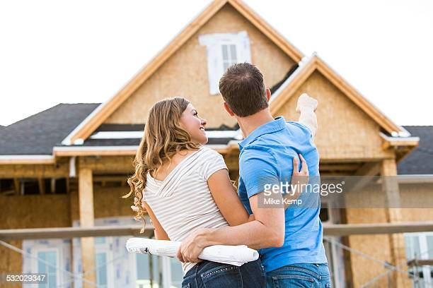 Caucasian couple admiring house under construction