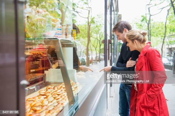 Caucasian couple admiring pastries in bakery window