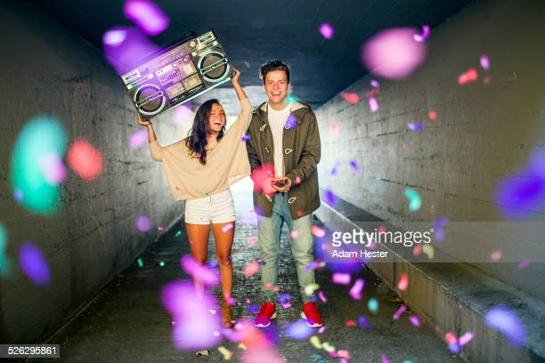 Caucasian couple carrying boom box and throwing confetti in tunnel