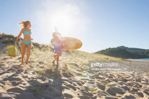 Caucasian couple carrying surfboard and bag on beach
