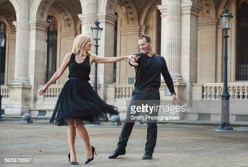 Caucasian couple dancing in courtyard : Stock Photo