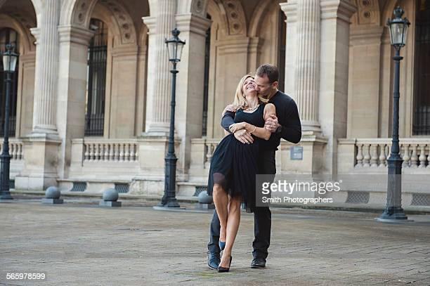 Caucasian couple dancing in courtyard