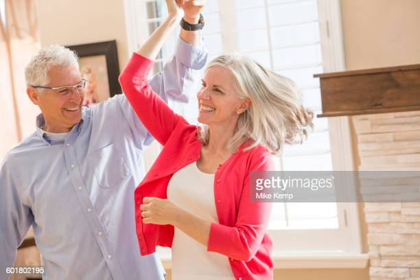 Caucasian couple dancing in living room
