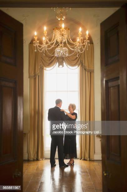 Caucasian couple dancing in mansion room