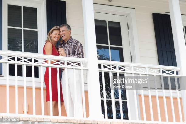 Caucasian couple dancing on balcony