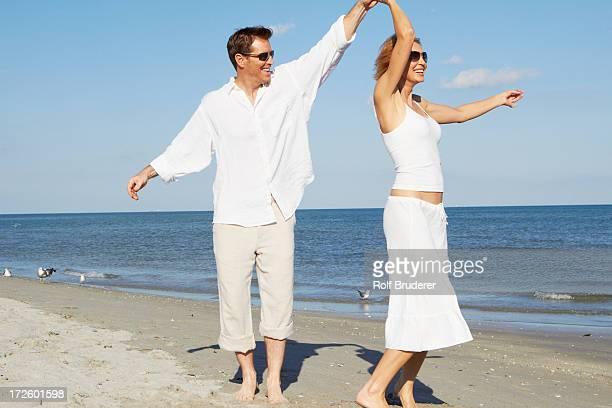 Caucasian couple dancing on beach