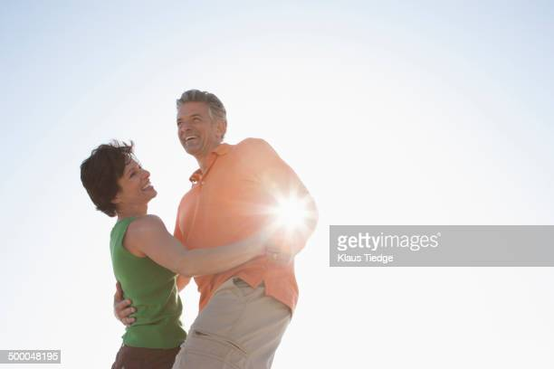 Caucasian couple dancing outdoors