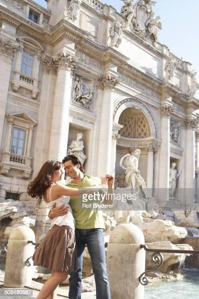 Caucasian couple dancing outside Fontana di Trevi, Rome, Italy