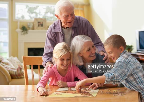 Caucasian couple doing puzzle with grandchildren