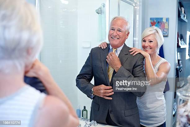 Caucasian couple dressing in bathroom