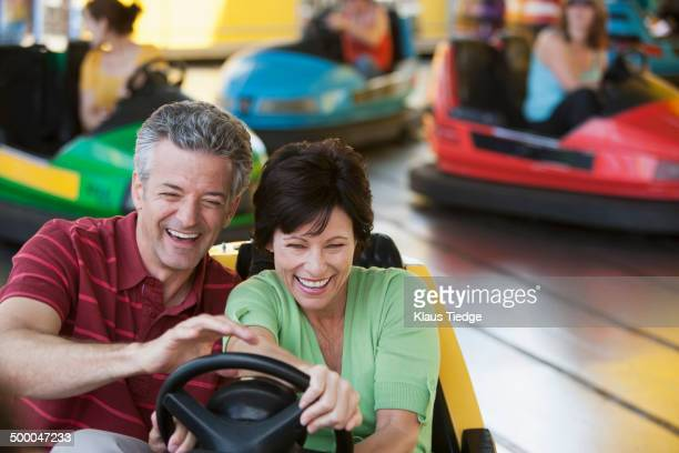 Caucasian couple driving bumper car