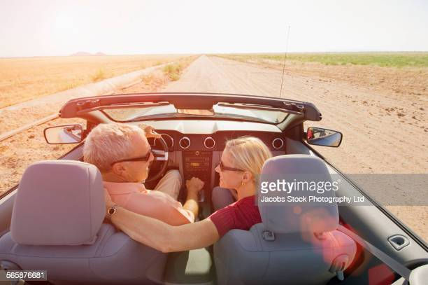 Caucasian couple driving convertible on desert road