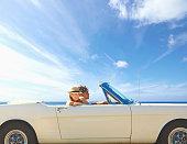 Caucasian couple driving convertible under blue sky