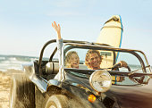 Caucasian couple driving jeep on beach