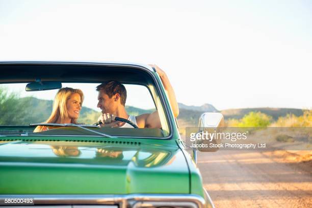Caucasian couple driving truck on rural road