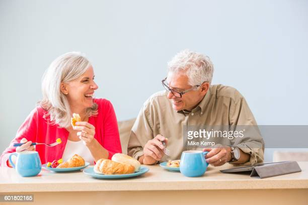 Caucasian couple eating at table
