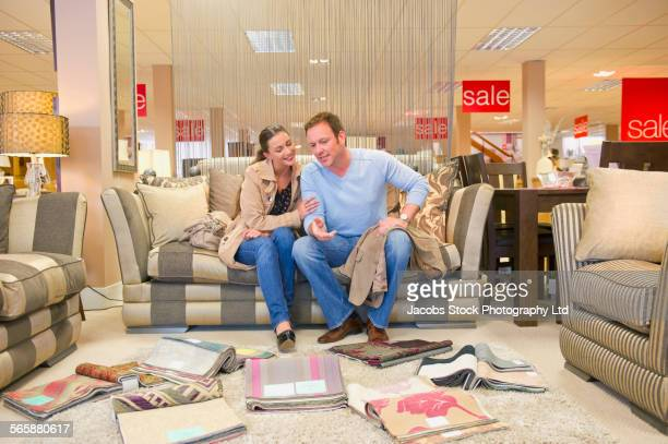 Caucasian couple examining fabric swatches in furniture store