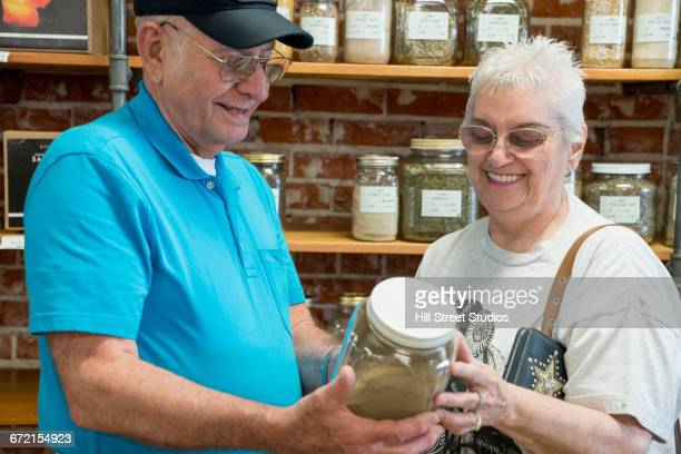 Caucasian couple examining jar in nutrition store