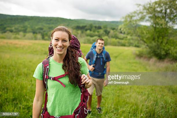 Caucasian couple hiking in rural field