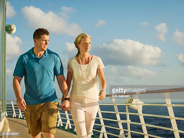 Caucasian couple holding hands on boat deck