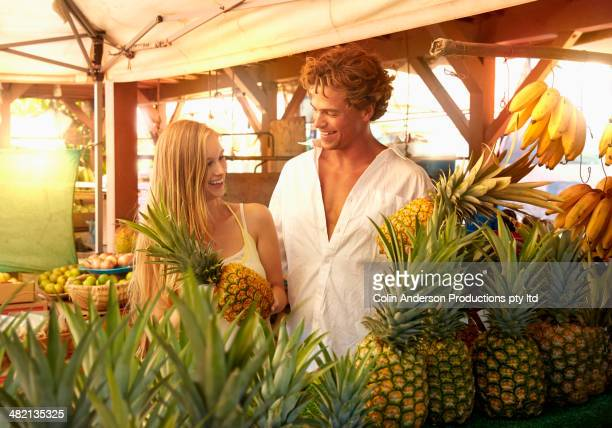 Caucasian couple holding pineapple at produce stand